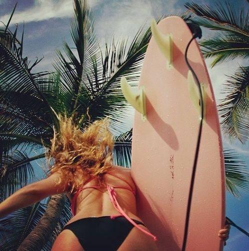 chica con tabla de surf de espaldas