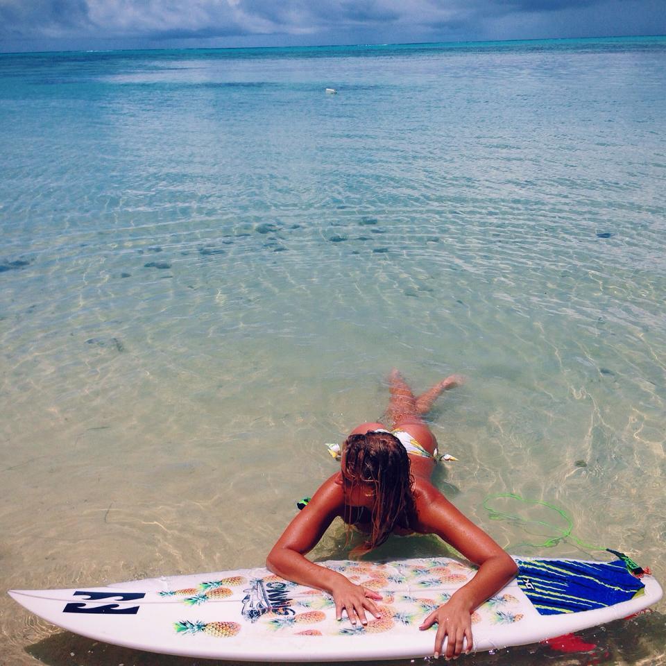 chica con tabla de surf estirada