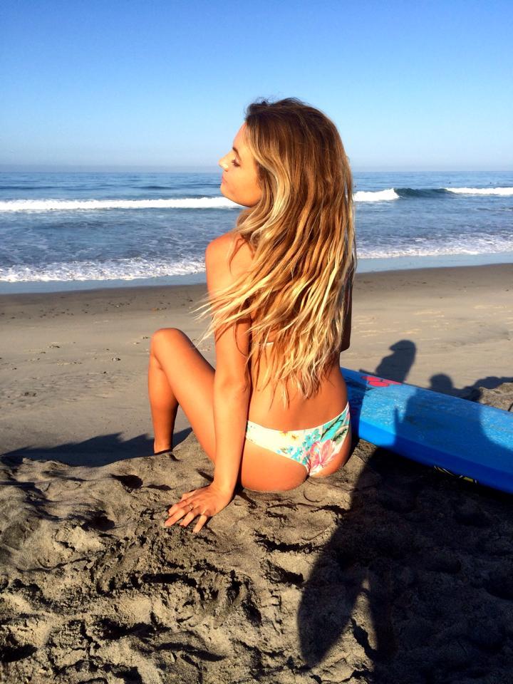 chica con tabla de surf sentada